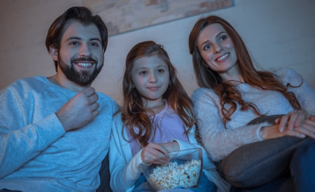 a family eating popcorn on the couch watching a movie in the dark